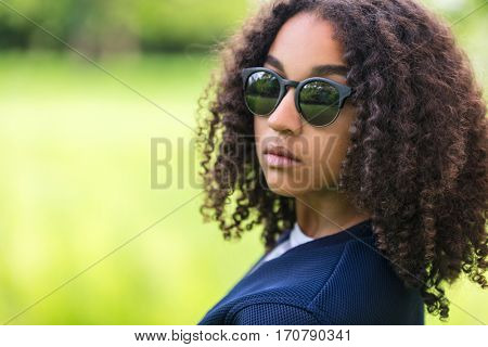 A beautiful sad moody mixed race African American female girl child teenager young woman in sunshine wearing sunglasses with attitude