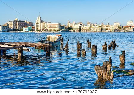 The City of Havana in Cuba with a view of the Old Havana skyline and an old wooden pier with fishing boats on the bay