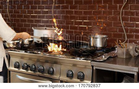 Chef is making flambe dish in restaurant kitchen