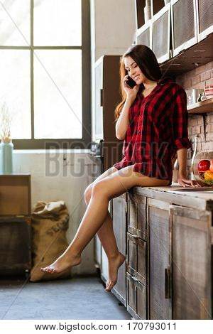 Vertical image of woman in red shirt with naked legs talking at phone and sitting on table in kitchen. Full length. Side view