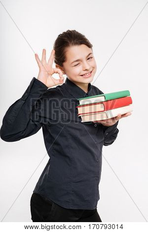 Photo of pretty young girl holding books and make okay gesture isolated over white background.