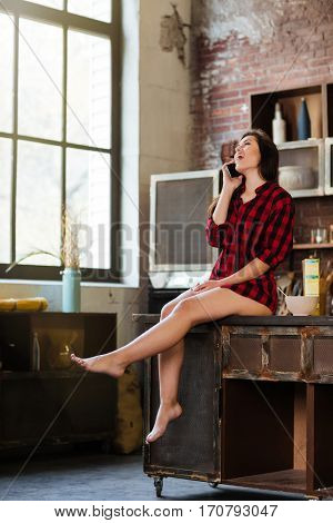 Full length young pretty woman in red shirt with naked legs talking on phone and sitting on the table in kitchen. Side view