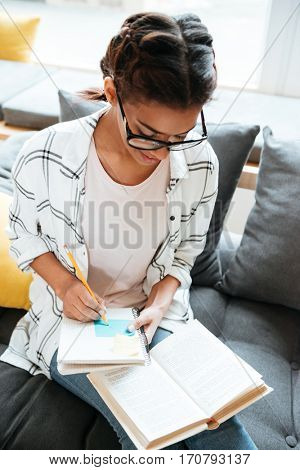 Picture of young amazing african lady wearing glasses sitting in library holding book and writing notes.