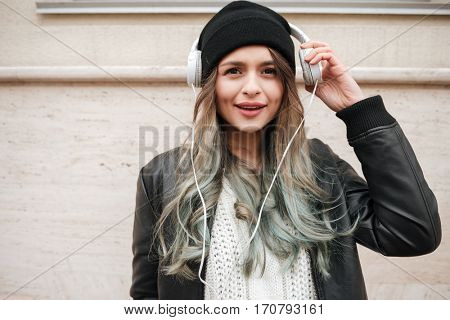 Funny Woman in warm clothes listening music in headphone on the street and looking at camera