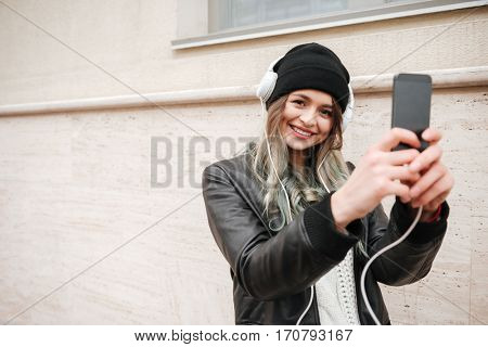 Smiling Woman in warm clothes and headphone making photo on her smarphone on the street