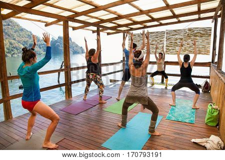 SAN MARCOS, GUATEMALA-DEC 24, 2015: Yoga classes at Atitlans lake shore in San Pedro on Dec 24, 2015, Guatemala. Participants perform yoga on banch lake.