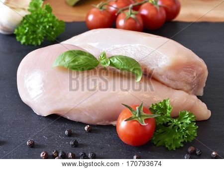 Raw chicken breast on a slate plate, with fresh cherry tomatoes, garlic and herbs. Cooking ingredients, healthy eating.