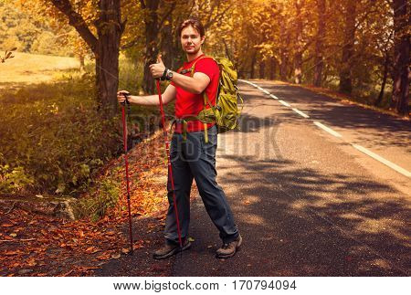 Young man tourist walking with sticks on road and showing thumbs up handsign