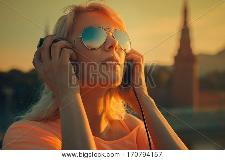 Young teenage style woman listening music at morning sunrise on city background