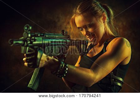 Young strong woman with big gun in dramatic urban interior. Tattoo on body.