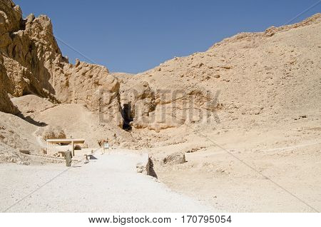 A custodian walks towards one of the tombs open to the public in the historic Valley of the Queens in Luxor Egypt. Ancient Egyptian royalty were buried in this valley in what was the city of Thebes.