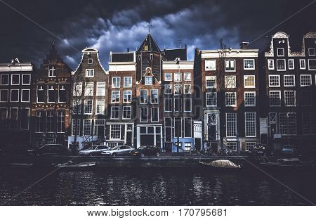 Front view of historical Amsterdam buildings across canal sun lit with dark clouds in background