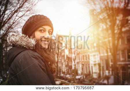 Young long haired woman standing outdoors in the street of Amsterdam in winter clothes looking back at camera and smiling. Portrait with warm light glowing effect