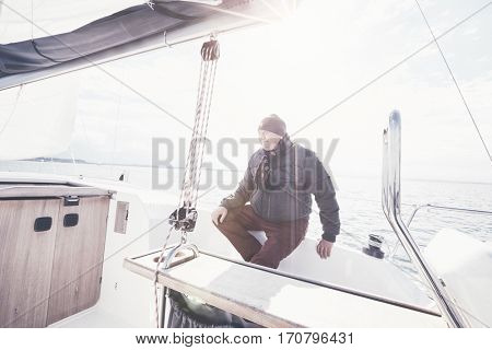 Senior man wearing jacket, scarf and hat, sitting on yacht cockpit and enjoying perfect autumn day under sails - sailing holidays concept