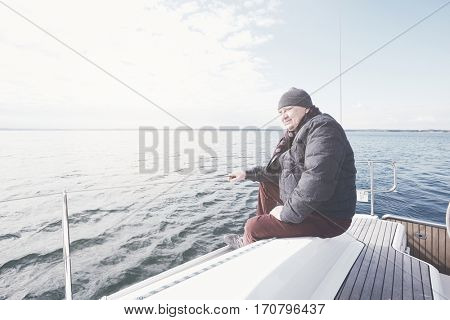 Senior man wearing jacket, scarf and hat, sitting on yacht stern and enjoying perfect autumn day under sails - sailing holidays concept