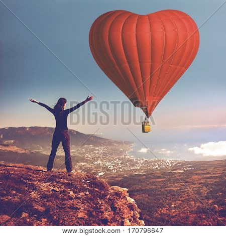 Girl with rised hands on the top of mountain looking at big air balloon in the sky. Romantic postcard background on Valentine's Day. Sport and recreation travel theme. Nature background. Back view