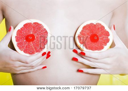woman naked with colorful background holding grapefruit