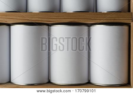 Rows of tin cans with unbranded blank white labels on wooden shelves.