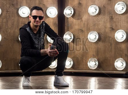 Male Singer In Sunglasses Performs On Scene In Projectors Lights