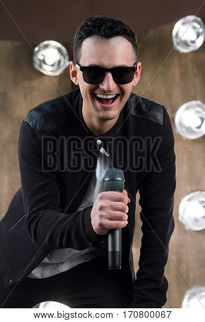 Male Singer In Sunglasses With Microphone Sings In Projectors Lights