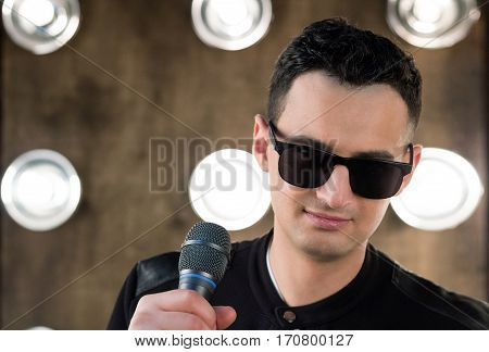 Male Singer In Sunglasses With Microphone Performing In Projectors Lights