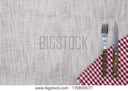 The background to create the restaurant's menu. Linen tablecloth fork knife on a bright checkered cloth. Is used to create a menu for the steak restaurant
