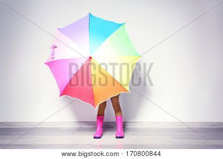 Cute little African American girl with umbrella in rubber boots against light wall. Fashion concept