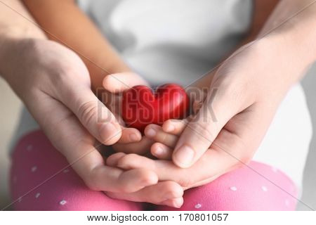 Child and adult person holding small red heart, closeup. Adoption concept