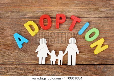 Word ADOPTION and figure in shape of happy family on wooden background