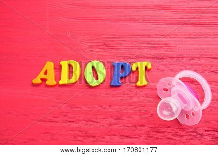 Word ADOPT and passifier on color wooden background