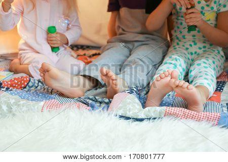 Cute little children blowing soap bubbles in hovel, closeup
