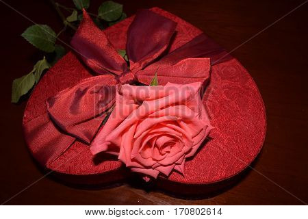 close up of pink rose on top of heart shaped red box with red bow