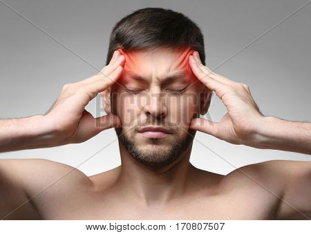 Young man suffering from head ache on gray background. Health care concept