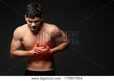 Young man suffering from chest pain on black background. Health care concept