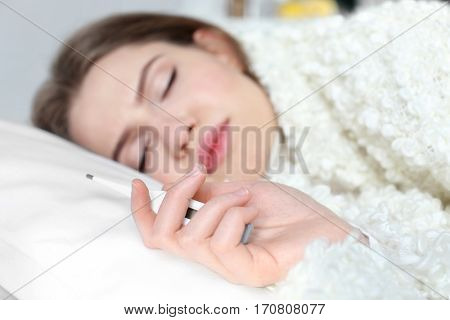 Young ill woman with electronic thermometer sleeping in bed at home, closeup