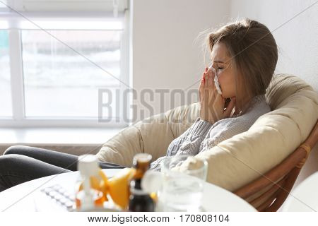 Young ill woman with tissue sitting on lounge at home
