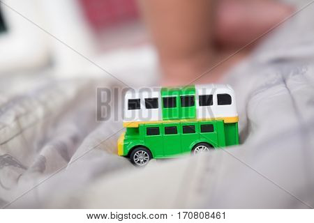green double decker bus toys with baby foot background