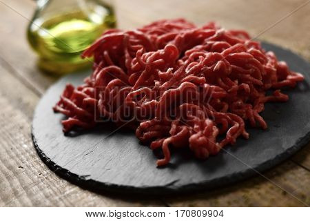 raw beef ground meat on a slate plate and a glass cruet with olive oil, on a rustic wooden table