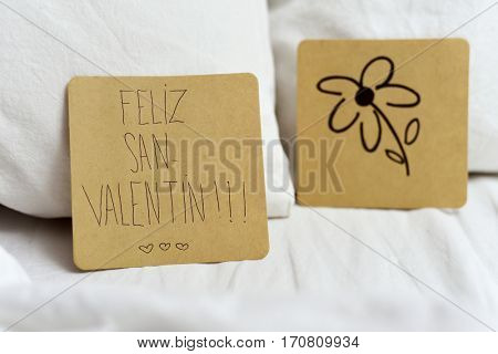 closeup of a brown paper note with the text feliz san valentin, happy valentines day written in Spanish and a flower drawn in another note, on the white sheets of an undone bed
