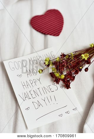 closeup of a white paper note with the text good morning and happy valentines day written in it, a red heart and a bunch of dried flowers, on the white sheets of an undone bed
