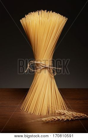 Dry Pasta And Wheat On Dark Wooden Table On Grey