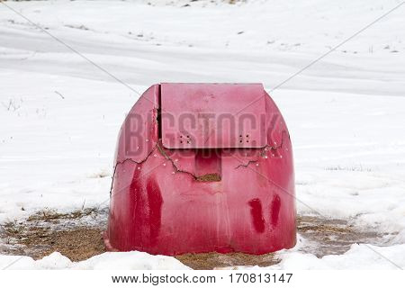 Broken red container for grit and salt in winter time