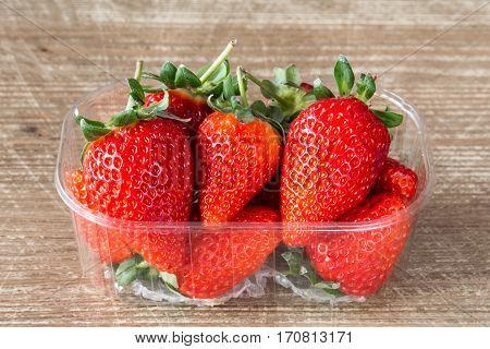Plastic box full of red fresh strawberries