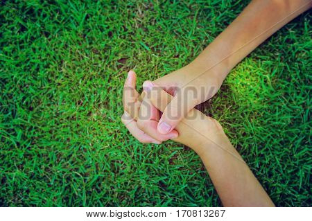 Asian boy hands clasped together on green grass