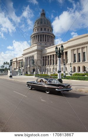 Havana Cuba - January 22 2017: Street scene in downtown Havana with a view of the Capitol building and old cars on the road