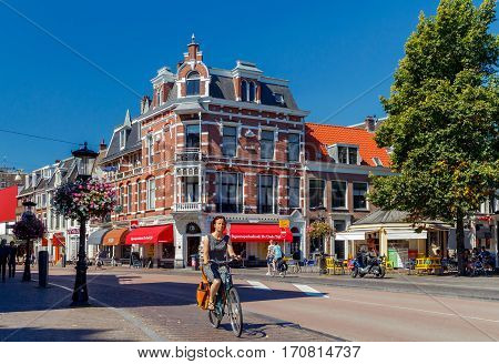 Utrecht, The Netherlands - August 24, 2016: A woman on a bicycle on the main street in Utrihte. Bicycles are the main means of transport in the Netherlands.