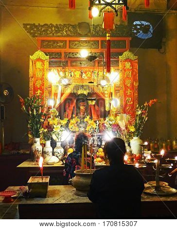 Sheung Wan, Hong Kong - February 10, 2016: Two women pray at an altar inside the Man Mo Temple in Sheung Wan, Hong Kong.