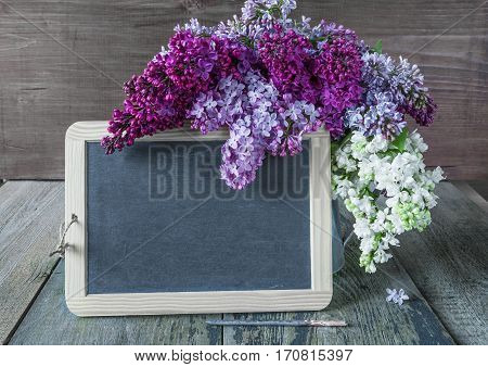 Blank chalkboard and lush multicolored bouquet of lilac flowers in a metal pitcher on an old wooden background