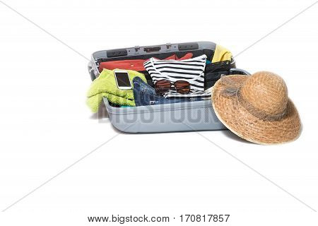 Studio shot of a suitcase packed with clothes shirts straw hat and a smart phone. Everything is on a white background.