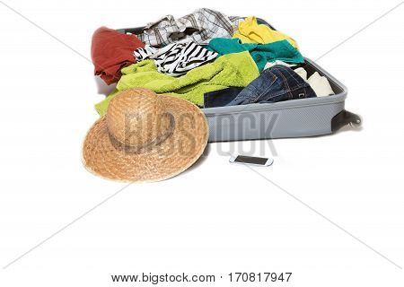 Studio shot of a suitcase with scattered clothing straw hat and a smart phone are lying in front of the suitcase. Everything is on a white background.